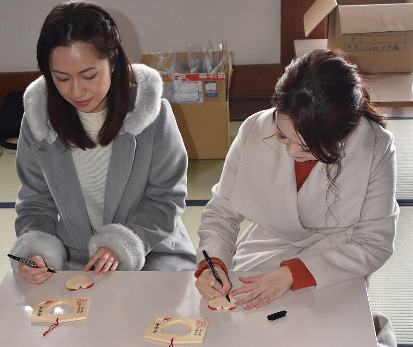 愛染寺本堂で、「赤いハート」の裏に願い事を書く参拝者たち