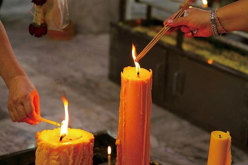 同寺院の参拝者は、ロウソクの火を使って線香などに火を灯す