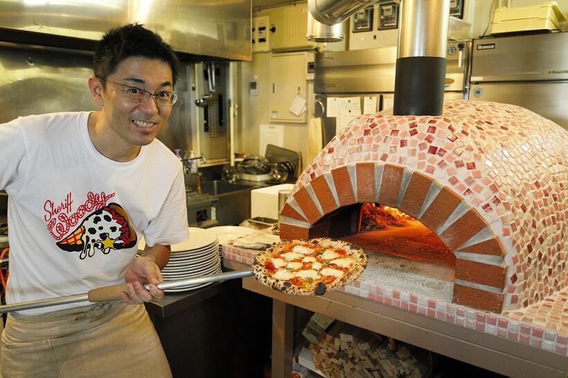 「piazza」の店主・和田穂高さん。窯から出したばかりの熱々のピザ、おいしそう!