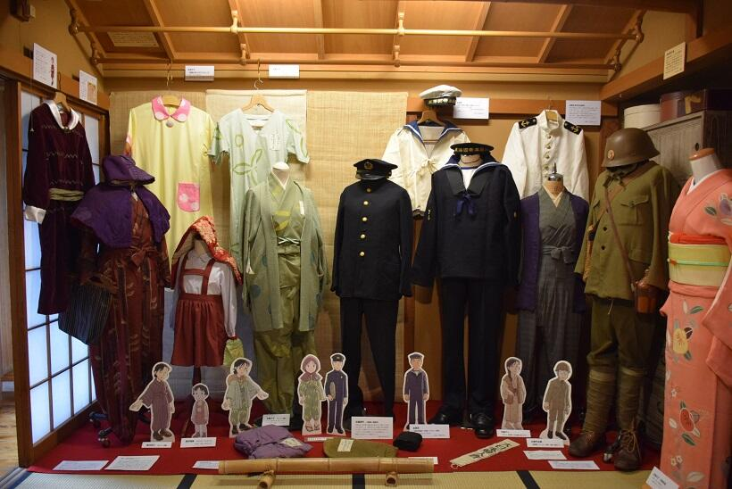 作中人物の衣装。手前左から3つ目が「すずさん」のもんぺや羽織。右から4つ目が「水原さん」の水兵服