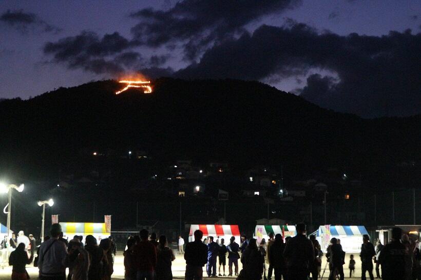 11月9日、東広島市安芸津町の保野山の山頂近くで赤く燃えさかる「万」の火文字