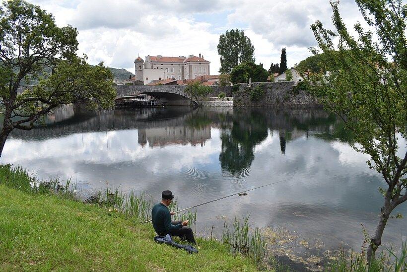 川で釣りをする人。川面に建物や橋が映る