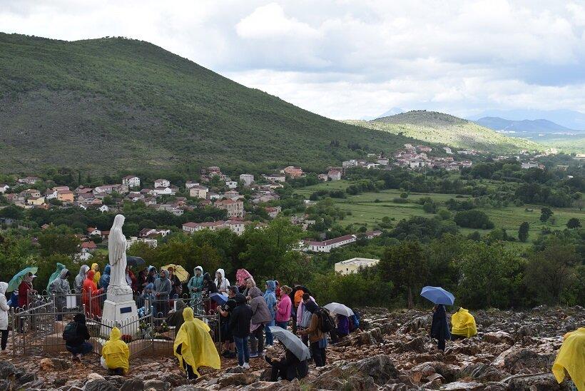 「幻視者」の一人とともに山に登り、聖母マリア像の回りで祈りを捧げる巡礼者