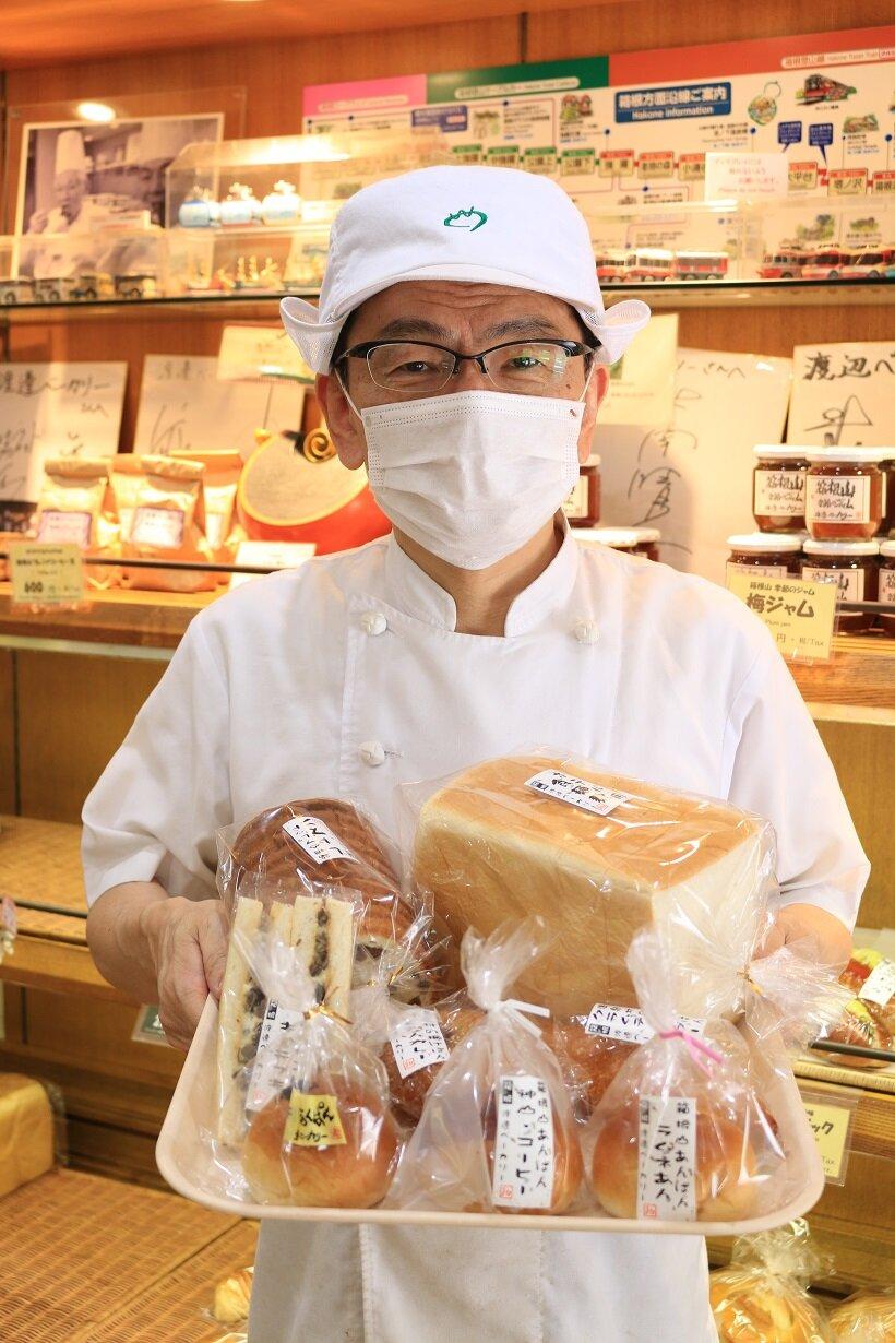 自慢のパンを手にする5代目主人・渡邊貞明さん