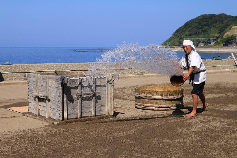 登谷良一さんが「ザザッ、ザザッ」とリズムよく海水を砂にまく音に熟練の技を感じる