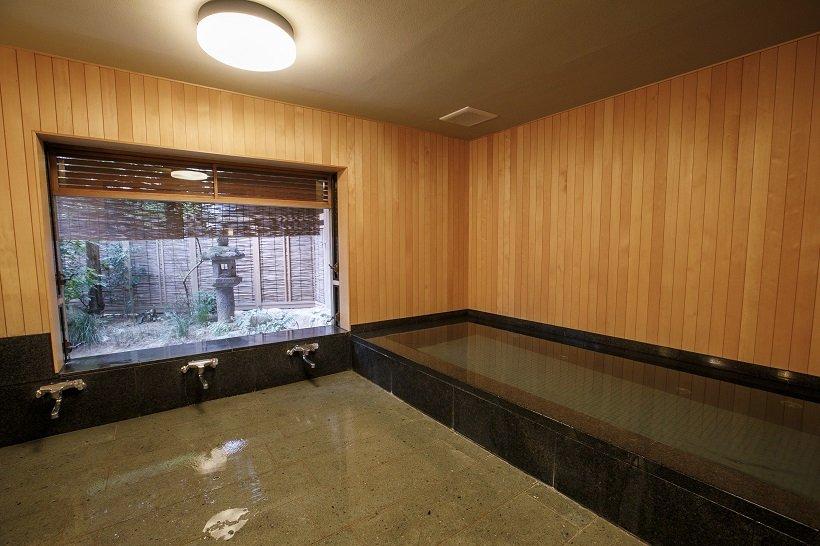 ヒノキの壁、黒御影石の湯船、福光石の床など大浴場にもこだわりを感じる