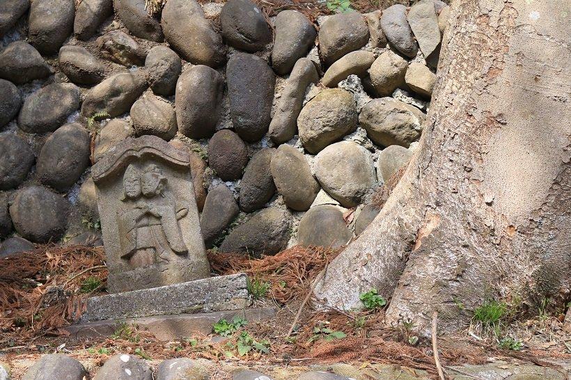 坂下道祖神は、木の根の成長で押し上げられ傾いていた